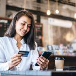 mulher com cartão de crédito e celular na mão